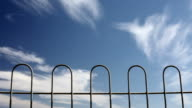 Metal fence with blue skies and clouds time lapse video