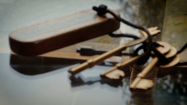 Metal Keys, Wooden Key ring pull focus on glass table video
