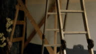Metal stepladder stands in empty room which is prepared for reconstruction video
