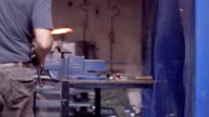 Metal worker witih hammer forging hot iron at anvil video