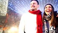 Mid 20's couple enjoying a walk on winter night. video