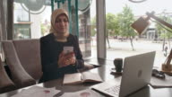 Mid adult Arab businesswoman making phone call in cafe video