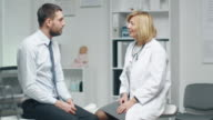 Mid Adult Female Doctor Consults Young Man About His Back Pain. video