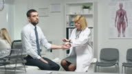 Mid Adult Female Doctor Manually Checks Male Patient's Pulse. video