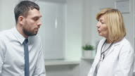 Mid Adult Female Doctor Talks Seriously with Her Male Patient. video