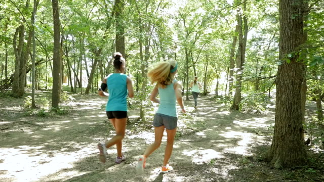 Mid adult fitness instructor leading off road running club during jog outdoors video