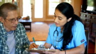 Mid adult Hispanic home healthcare nurse reviews information with senior patient video