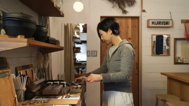 Mid adult woman working in a small general shop video