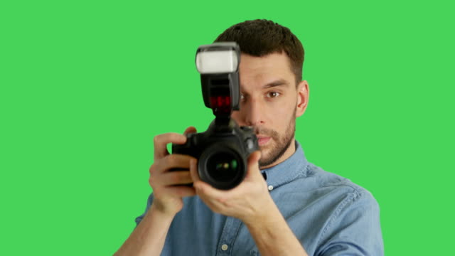 Mid Closeup Shot of a Handsome Photographer Taking Pictures with His Camera. Shot on Green Screen. video