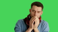 Mid Closeup Shot of a Sick Man in Scarf Caughing and Sneezing. Background is Green Screen. video
