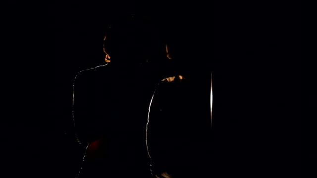 Mid shot of a girl boxing actively in the dark with a single projector. video