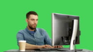 Mid Shot of a Stylish Man Internet Browsing and Sipping Coffee Sitting at His Desktop. Shot on Green Screen Background. video