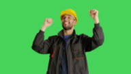 Mid Shot of a Worker Wearing Hard Hat Dancing and Raising His Hands. Background is Green Screen. video
