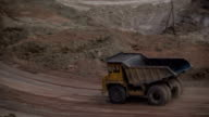 Mid shot of heavy mining trucks carring cargo in opencast mining quarry in sunny summer day. Bouxite mining quarry. video