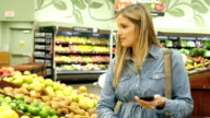 Mid-adult Caucasian female customer in produce department in local supermarket checks grocery list on her smart phone video