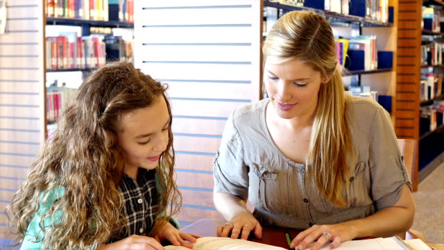 Mid-adult Caucasian home school mother helps daughter with reading assignment in library video