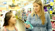 Mid-adult Caucasian mother and her Hispanic elementary age daughter shop in personal care aisle of supermarket video