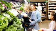 Mid-adult Caucasian mother and mid-adult Hispanic father shopping with three young daughters in local supermarket video
