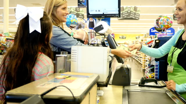 Mid-adult Caucasian mother hands cash to young Caucasian female cashier to complete transaction at supermarket video