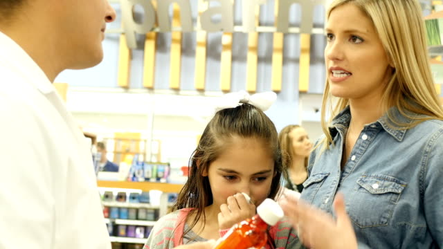 Mid-adult Caucasian mother seeks advice from mid-adult Hispanic pharmacist about her Hispanic elementary age daughter's cold symptoms video