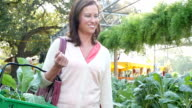 Mid-adult Caucasian woman strolls confidently through farmer's market or plant nursery video
