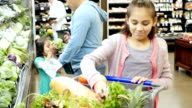 Mid-adult Hispanic father shops for produce with his elementary age and preschool age daughters at a supermarket video