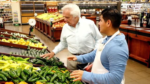 Mid-adult Hispanic male assists Caucasian senior customer as he shops for peppers in local supermarket video