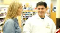 Mid-adult Hispanic pharmacist assists mid-adult Caucasian customer in supermarket pharmacy video