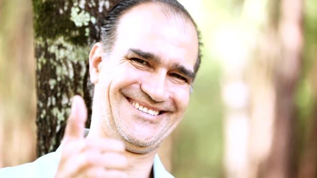 Mid-Adult Latin man walking into camera focus range - testimonial video