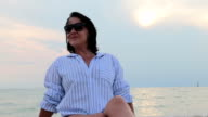mid-aged woman sitting on the beach near the sea and feeling relaxed video