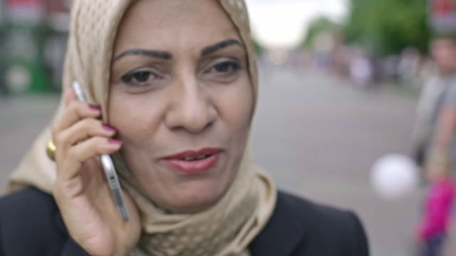 Middle adult Arab woman talking on phone video