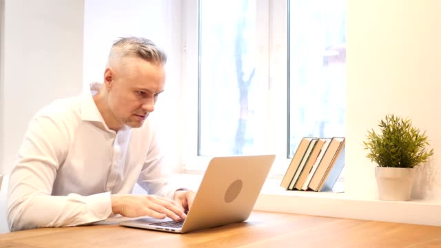 Middle Age Man Upset by Loss while Working on Laptop video