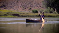 Middle age outdoorsman paddles a blue canoe down a river video