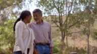 Middle aged black couple laugh while walking in countryside video