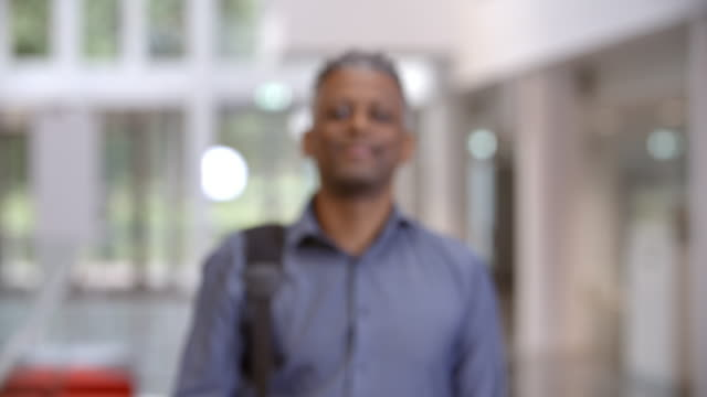 Middle aged black male teacher walking into focus in a lobby video