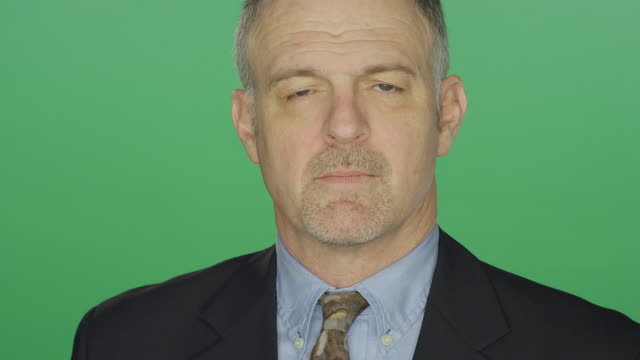 Middle aged businessman disappointingly staring, on a green screen studio background video