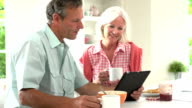 Middle Aged Couple Looking At Digital Tablet Over Breakfast video