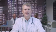 Middle aged male doctor on a video call from his office video