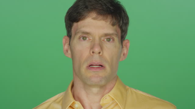 Middle aged man looking sad, on a green screen studio background video