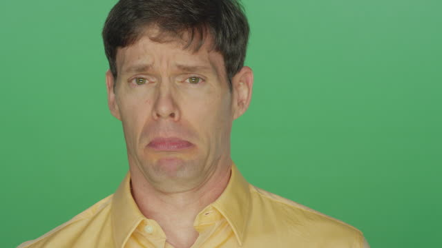 Middle aged man making funny faces, on a green screen studio background video