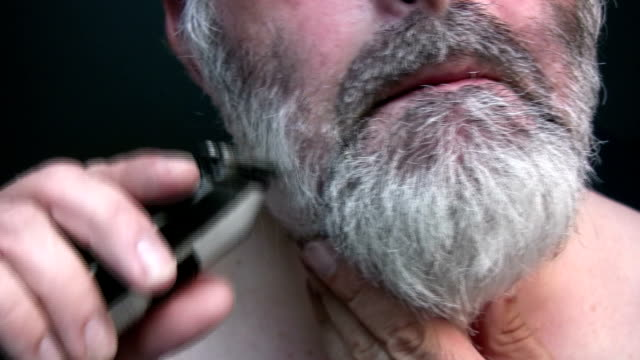 Middle aged man with grey hair trimming beard and moustache. video