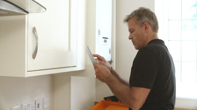 Middle aged technician with digital tablet servicing boiler video