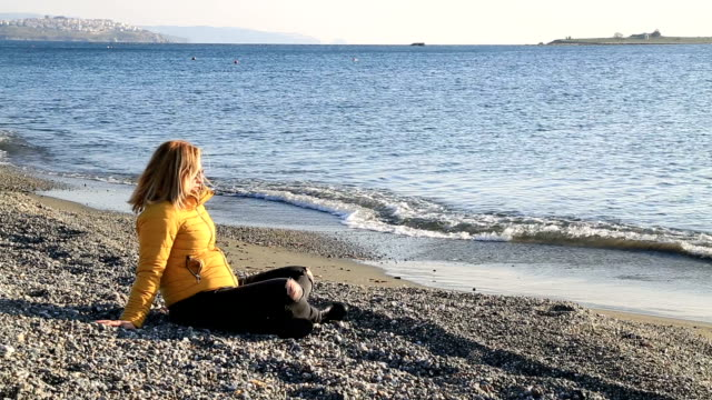 Middle aged woman resting at winter beach video