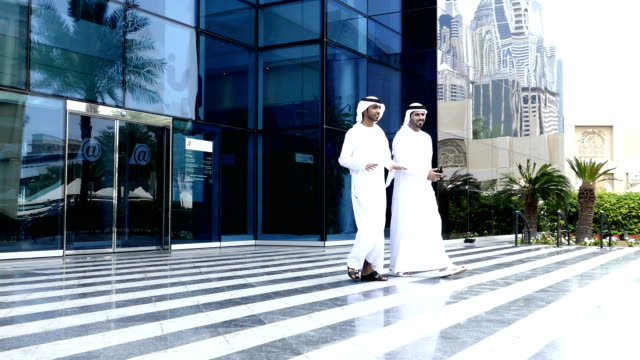 Middle eastern business people walking on the street - Slowmotion video