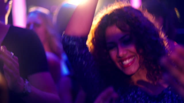 Middle eastern woman dancing and laughing at party in nightclub video