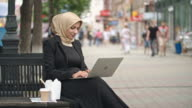 Middle Eastern woman working on laptop outdoors video