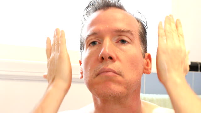Middle-aged Caucasian male applying moisturizing anti aging product HD video