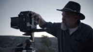 Middle-Aged Caucasian Male Outdoor Photographer Adjusting Camera video