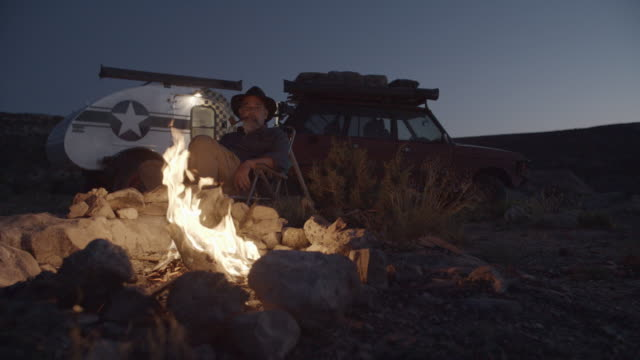Middle-Aged Caucasian Male Smokes Pipe by Campfire video