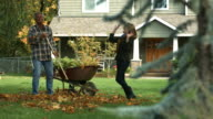 Middle-Aged couple raking leaves and having fun video